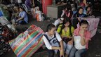 People sit with their belongings at a bus station as they wait to move out of Bangkok on Friday