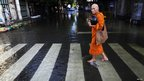 A Buddhist monk walks in a flooded street to collect morning alms outside the Grand Palace in Bangkok on Friday