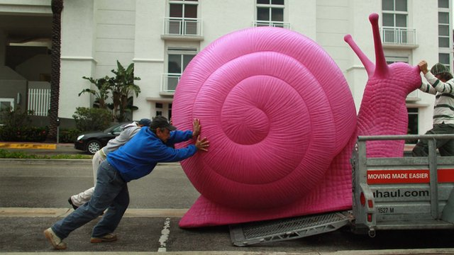 Group of men push an enormous pink snail onto a trailer