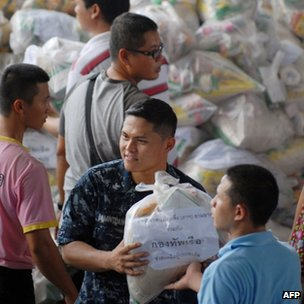 A sailor from the USS Mustin (centre) hands food aid to local Thai residents