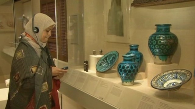 Woman listening to audio guide in front of Islamic art display