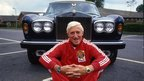 Jimmy Savile sitting in front of a Rolls Royce car.