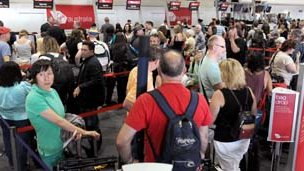 Passengers queue at Virgin Australia check-in counters at Perth airport