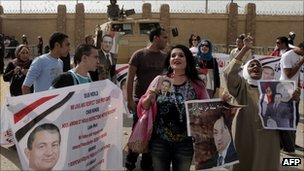 Egyptians supporters of former President Hosni Mubarak gather outside the courts set up at the Police Academy