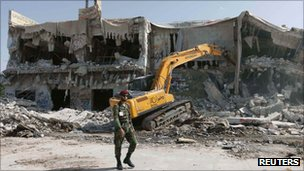 A soldier walks past the house of former leader Muammar Gaddafi as it is demolished by a bulldozer in Tripoli