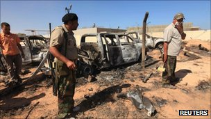 Anti-Gaddafi fighters stand in front of damaged cars after an attack by Nato on Gaddafi's convoy in Sirte