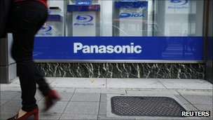 A woman walks past a Panasonic window display