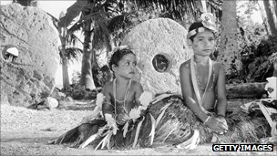 girls sit infront of stone money, circa 1955