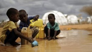 This file picture taken on 16 October 2011, shows Somali boys fetching water from a puddle that formed after rain at the IFO-2 complex in the sprawling Dadaab refugee complex in Kenya.