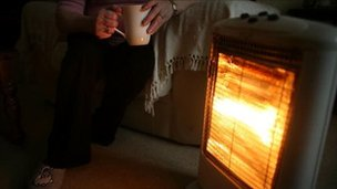 A heater and a man holding a cup of tea