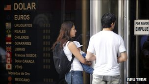 A couple wait outside a closed foreign exchange house in the Argentine capital, Buenos Aires