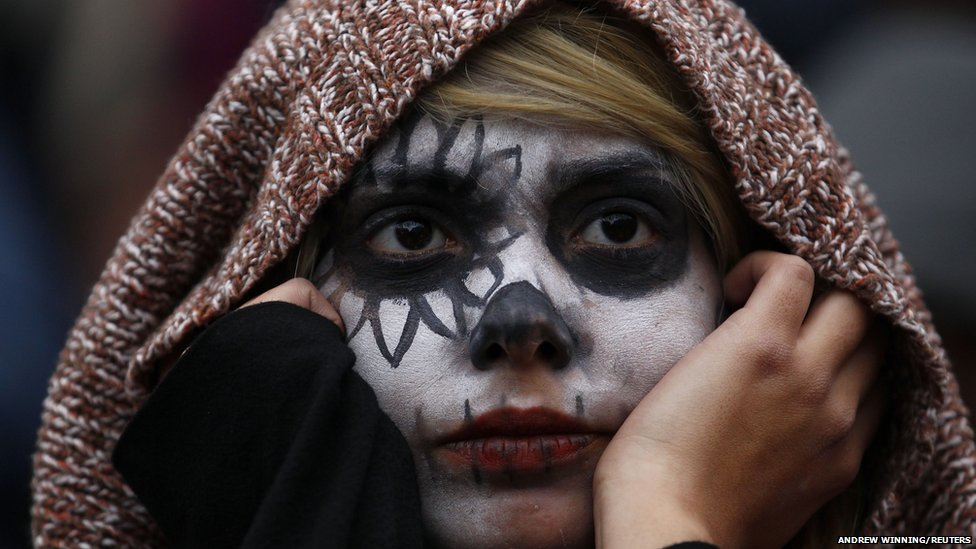 An anti-capitalist protester wearing face paint listens to a speaker
