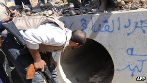 Anti-Gaddafi fighter looks into storm drain in which Col Gaddafi was allegedly captured in October 2011, near the coastal city of Sirte