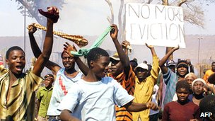 """Residents wave """"no more eviction"""" placard in Porta Farm slum, west of Harare, July 2005"""