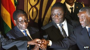 Robert Mugabe, Morgan Tsvangirai and Thabo Mbeki (from left to right) pose after signing of power-sharing accord in Harare, 15 September 2008