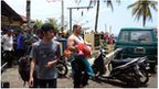 In this handout photograph released by Pikiran Rakyat, an unidentified survivor carrying a child is escorted at a marine police station on the coast of Pangandaran town in Indonesia's West Java province on November 1