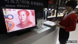 An employee operates a camera to zoom in on the image of a Chinese 100 yuan banknote at a production exhibition in Wuhan, Hubei province, on 13 October 2011