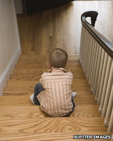 Young male child sitting alone on stairs of his home
