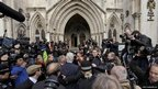 Wikileaks founder Julian Assange is surrounded by media, aides and police as he arrives for his hearing at the High Court in London