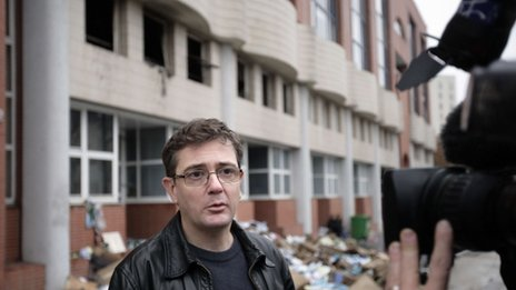 Charlie Hebdo's publisher, Charb, talks to journalists in Paris, in front of the magazine's offices, after they were destroyed by a petrol bomb attack overnight, 2 Nov 2011