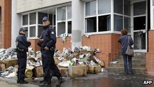French police stand in front of the damaged offices of French satirical magazine Charlie Hebdo in Paris 2 November 2011.