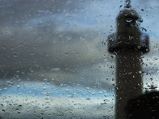 Rain falling from blue and grey sky with lighthouse in foreground