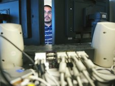 Computer forensic examiner Gil Moreno works on several hard drives association with a crime