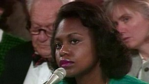Anita Hill sits at a microphone