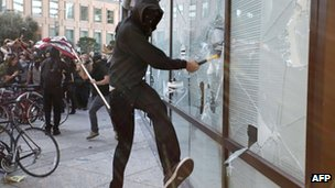 A masked protester smashes a window at a bank in Oakland. Photo: 2 November 2011