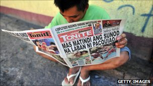 Man reads a paper on a Manilla street