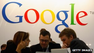 Computer users in front of a Google logo at Frankfurt Book Fair