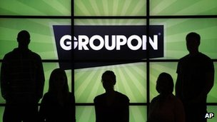 Groupon staff in front of logo