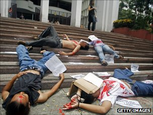 Filipino student activists lay on the ground acting as dead bodies