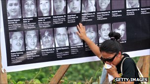 Bereaved woman stands by poster of faces of victims of 2009 massacre 