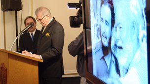 Cuban diplomat speaks at a podium in front of a photo of Fidel Castro and Ernest Hemingway