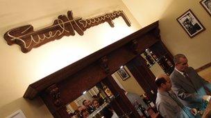 Bartenders fix drinks under an Ernest Hemingway sign