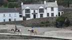 A pub and two horse riders in Little Haven