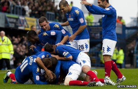 Erik Huseklepp is mobbed by his Portsmouth team-mates after scoring