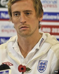 Peter Crouch displays a poppy on his England tracksuit in 2009