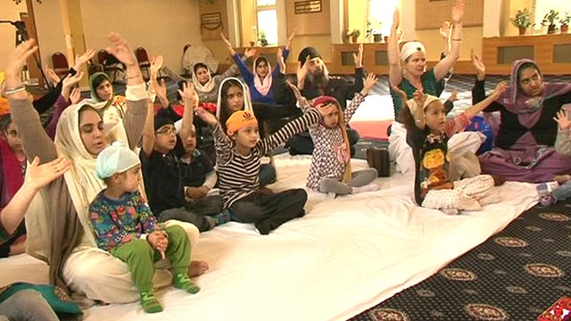 Children and their mothers worshipping at a Sikh temple in London