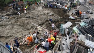 Rescue workers search the mid for survivors of a landslide