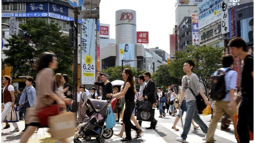 Pedestrians cross a road in front of the Shibuya station in Tokyo