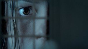 Rebecca Hall peers through a doll's house window in The Awakening
