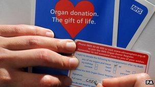 Person signing organ donation card