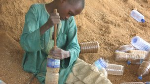 A child in Yelwa packing bottles with sand