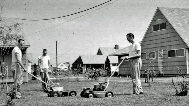Men pushing lawn-mowers in 1950&#039;s Levittown