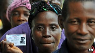 A woman shows her voter card as she waits in a queue in Monrovia to cast her ballot (8 November)