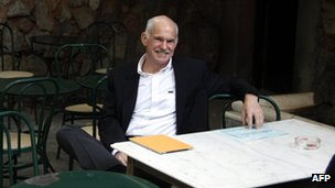 Greek Prime Minister George Papandreou smiles as he sits in a cafe at the national garden in Athens, near his office after the cabinet meeting on November 8, 2011