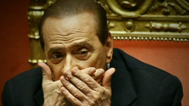 Berlusconi with hand over mouth