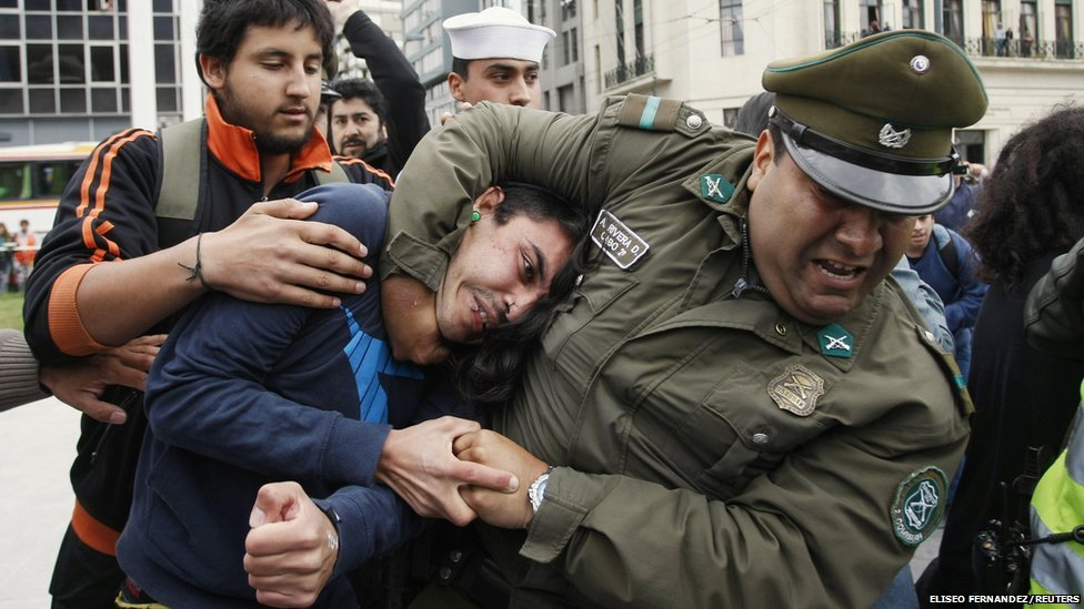 A police officer detains a student during a protest